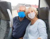Ehepaar im Zug mit Mund-Nasen-Schutz