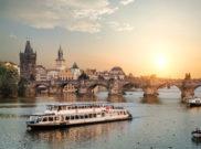 Ausflugsschiff auf der Moldau vor der Prager Altstadt im romantischen Sonnenuntergang
