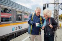 Reisende stehen vor dem alex Zug auf dem Bahnsteig