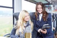 Die Kundenbetreuerin verkauft dem Fahrgast in der oberpfalzbahn einen Fahrschein direkt am Platz