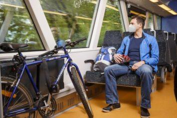 Person sitzt im zug mit einem fahrrad FFP2 V1
