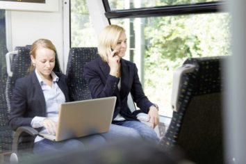 Zwei Pendler fahren mit der waldbahn, eine Person tippt etwas auf dem Laptop die andere Person telefoniert