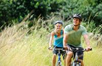 Ein Paar fährt mit dem Fahrrad über eine Wiese mit sehr langem Gras
