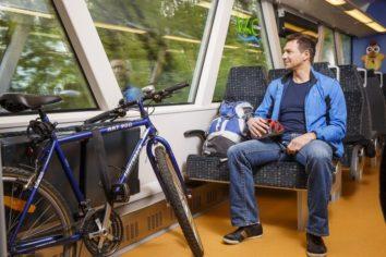 Ein Mann sitzt mit seinem Rucksack im Zug, vor ihm hat er sein Fahrrad an der Seite des Zuges abgestellt und fest gemacht