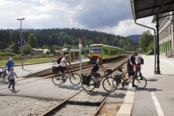 Fahrradfahrer sind mit der waldbahn angekommen und fahren jetzt mit dem Fahrrad weiter