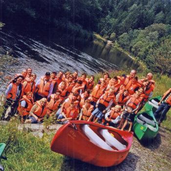 Eine Menschengruppe die am Ufer des schwarzen Regens steht zum Kanu fahren