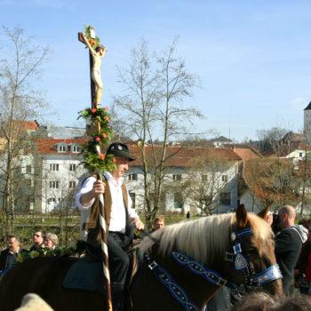 Beim Osterritt im Jahr 2007 in Regen sitzen Personen auf geschmückten Pferden und reiten durch Regen