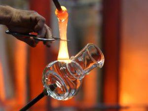 Ein Glashenkel wird an einer Glasvase befestigt