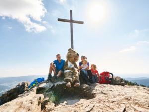 Das Gipfelkreuz am Großen Arber, daherum sitzen Wanderer