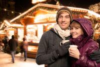 Zwei Menschen die an einem Weihnachtsmarkt sind und eine Tasse in der Hand halten