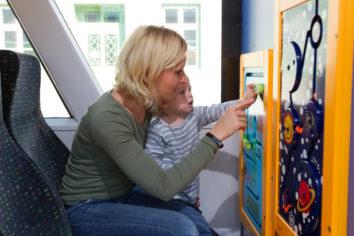 Mutter die mit ihrem Kind in der Kinderecke in der waldbahn spielt