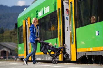 Mutter die mit dem Kinderwagen in die Waldbahn einsteigt