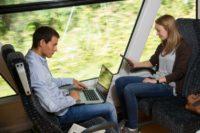 Zwei Personen im Zug, eine Person schaut ins Handy, die andere Person tippt am Laptop