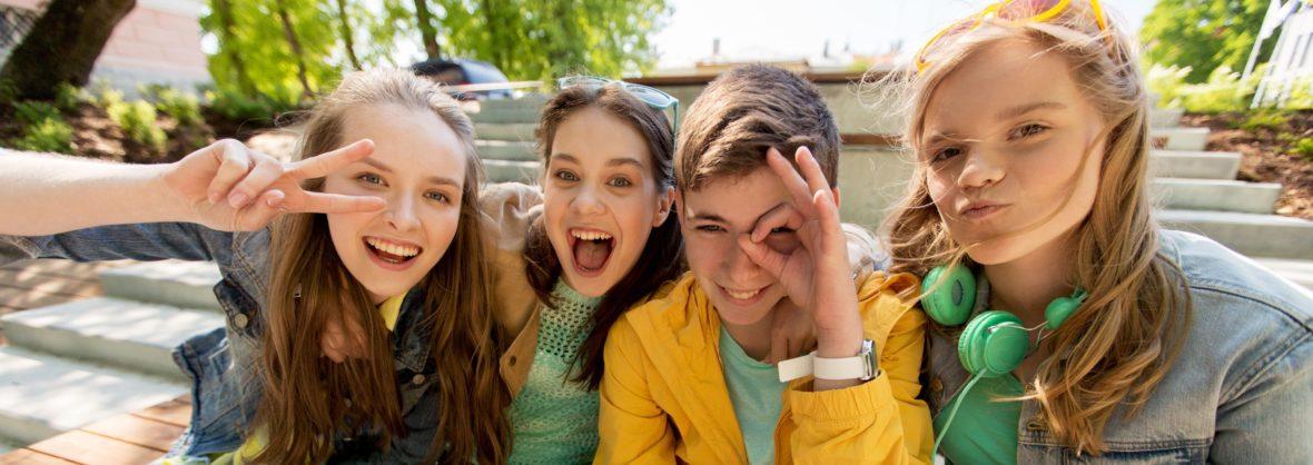 4 Jugendliche die nebeneinander sitzen