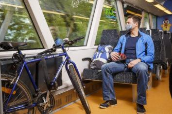Person sitzt im zug mit einem fahrrad Maske